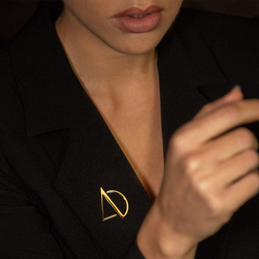 Spilla in ottone color oro marchio AD